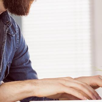 Bearded man typing on computer